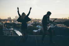 Couple In Rock N Roll Style Standing On The Rooftop And Enjoing Sunset, Girl Raised And Waving Hands At Blue Sky Background, Man Playing On Guitar. Concept Of Happy Young People.
