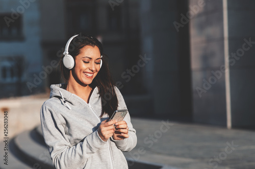 Young woman enjoys music via headphones on the street - 256283048