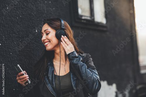 Young woman enjoys music via headphones on the street - 256283074