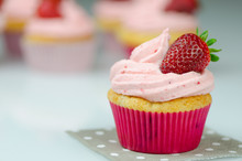 Delicious Pink Strawberry Cupcake With A Strawberry. Cupcakes And Pink Icing With A Strawberries On Top
