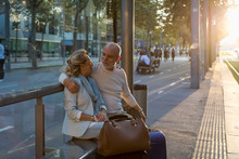 Spain, Barcelona, Senior Couple With Baggage Sitting At Tram Stop In The City At Sunset