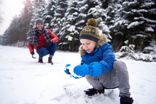 Father And Little Son Having A Snowball Fight In Winter Forest