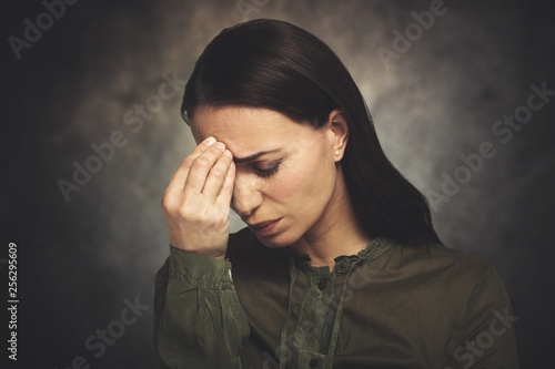 Young woman has headache on a grungy background
