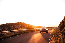 Spain, Classic Car Driving On Road During Sunset