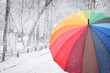Rainbow colored umbrella on winter street