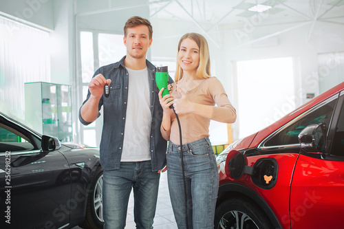Photo  Young smiling family buying first electric car in the showroom