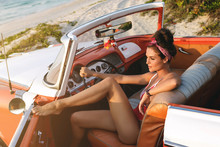Sexy Woman Wearing Red Swimsuit In Retro Cabriolet Car On The Beach.