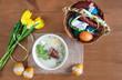 Śniadanie wielkanocne - barszcz biały z jajkiemi i kiełbasą, obok pisanki i koszyczek ze święconką