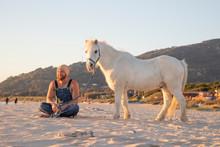 Spain, Tarifa, Happy Man With Pony Sitting On The Beach