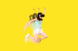canvas print picture - girl in VR glasses of virtual reality is jumping on a yellow background