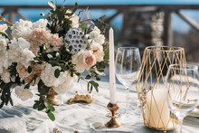 Luxury Decorated Table And Wedding Cake For A Romantic Date. Wedding Details: Tablecloth, Candles, Plates, Glasses, Near A Mountain River On Background. Wedding, Calligraphy Vintage, Top View.