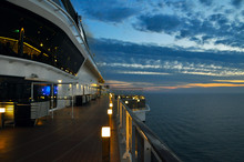 The Deck With The Lights Of A Cruise Ship On A Background Sunset
