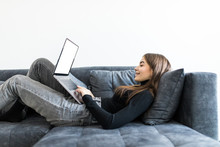 Young Smiling Woman Lying On Sofa With Laptop In Front Of Her In The Living Room