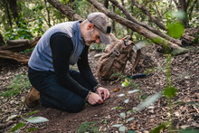 Man Making Fire With Tinder Polypore Fungus In A Forest