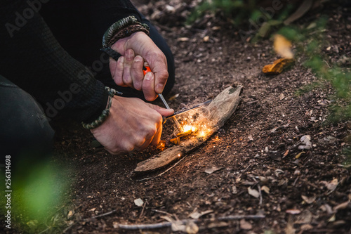 Fotografia, Obraz Man making fire with tinder polypore fungus in a forest