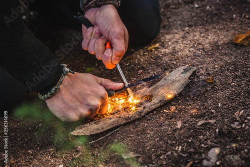 Fotografija Man making fire with tinder polypore fungus in a forest