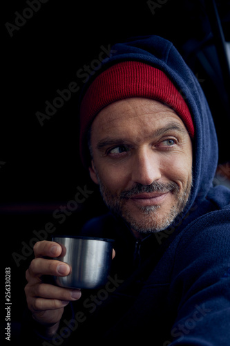 Portrait of bearded mature man with mug of thermos flask wearing red cap and blue hooded jacket