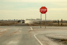 Country Roads - Stop Sign With Large Bullet Hole Stands By Crossroads With Pickup Truck With Trailer Driving Toward It In A Cloud Of Dust