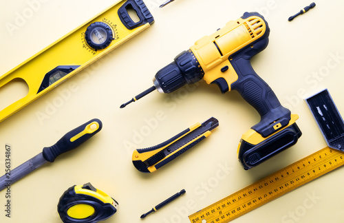 Flat layout of yellow hand tools on a yellow background. Wallpaper Mural