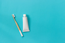 Natural Eco-friendly Bamboo Brush With White Bristles And Tube Of Toothpaste. Set For Washing On Paper Blue Background. Copy Space For Text Or Your Design Top View Flat Lay.
