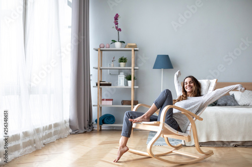 Happy woman resting comfortably sitting on modern chair in the living room at home.