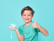 Leinwanddruck Bild - cool, pretty boy plays with homemade slime in front of a blue background and is having a lot of fun