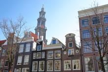 Crooked And Colorful Heritage Buildings, Located Along Bloemstraat Street, With Westerkerk Church Clocktower In The Background, Jordaan, Amsterdam, Netherlands