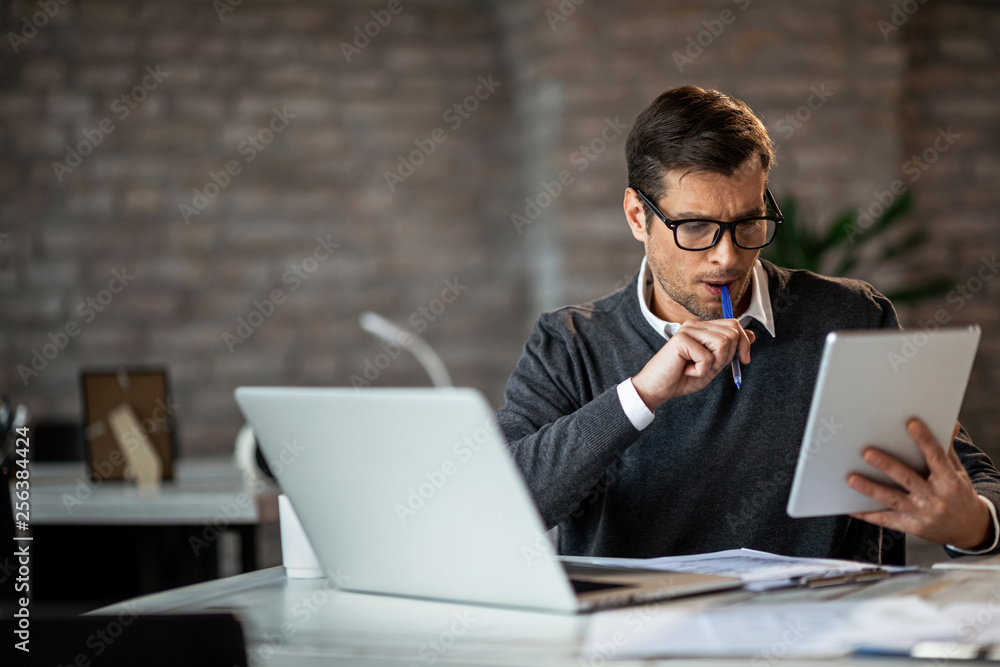 Fototapeta Mid adult businessman using digital tablet while working at his desk in the office.