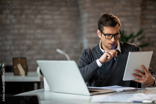 Fototapeta  Mid adult businessman using digital tablet while working at his desk in the office