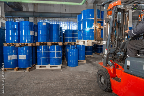 Foto blue barrels and red forklift in warehouse