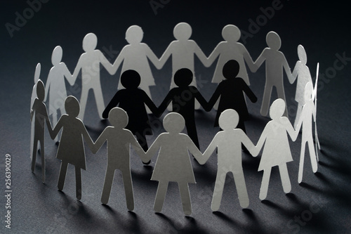 Three human paper figures surrounded by circle of paper people holding hands on dark surface Canvas Print