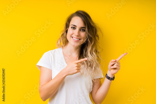 Fototapeta Young beautiful blonde woman over yellow background smiling and looking at the camera pointing with two hands and fingers to the side. obraz na płótnie