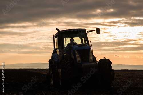 Poster de jardin Desert de sable Farmer plowing stubble field