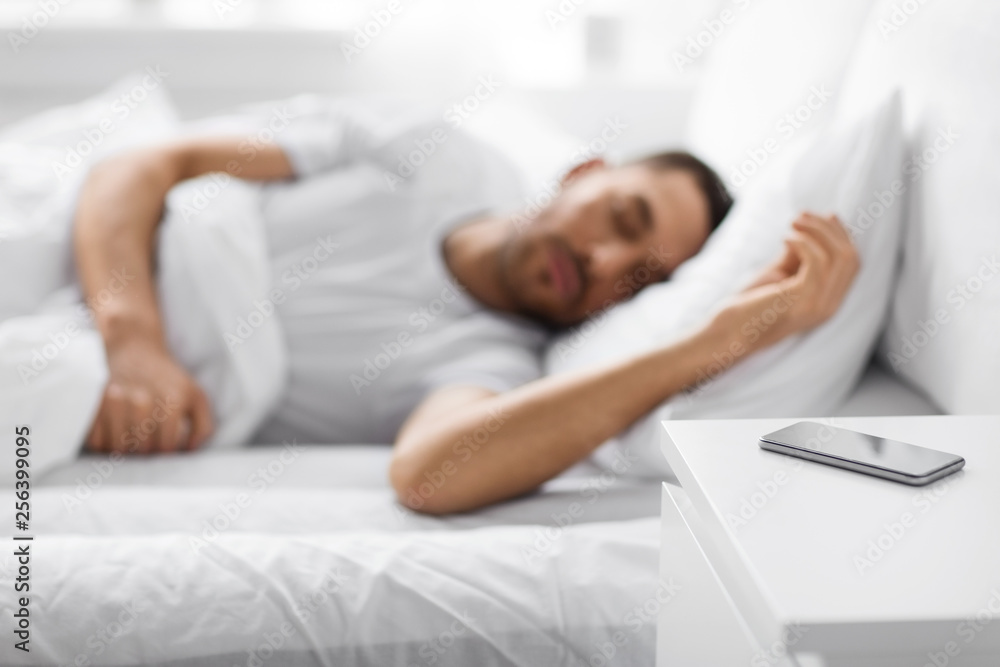 Fototapety, obrazy: technology and people concept - close up of smartphone on bedside table near young man sleeping in bed at home in morning