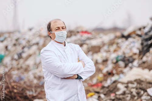 Valokuva  Caucasian ecologist in white coat and protective mask on standing with arms crossed on landfill and looking at camera