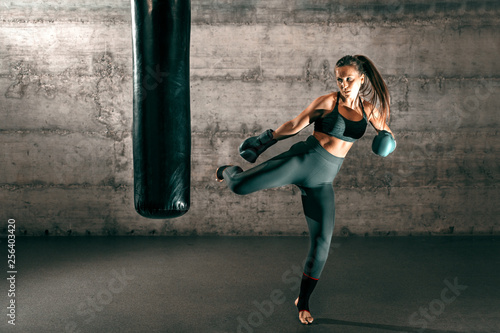 Cuadros en Lienzo Dedicated strong brunette with ponytail, in sportswear, bare foot and with boxing gloves kicking sack in gym