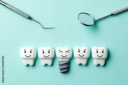 Photo Healthy white teeth and implants are smiling against green mint background and dentist tools mirror, hook