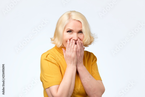 Fotografie, Obraz  senior female giggles joyfully, covers mouth as tries stop laughing
