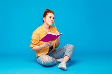 Education, High School, Inspiration And People Concept - Red Haired Teenage Girl In Checkered Shirt And Torn Jeans With Diary Or Notebook And Pencil Thinking Over Grey Background