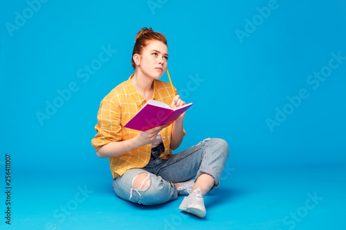 Obraz education, high school, inspiration and people concept - red haired teenage girl in checkered shirt and torn jeans with diary or notebook and pencil thinking over grey background - fototapety do salonu