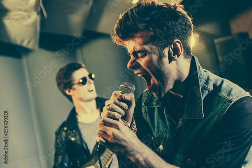 selective focus of stylish singer singing in microphone near rock band Wallpaper Mural