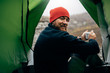 Leinwandbild Motiv Portrait of a view from tent entrance of young traveler man smiling and relaxing in mountains near to bonfire. Rear view of hiker male sitting in the camping tent, drinking hot beverage. Travel people