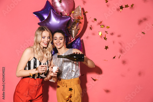 Photo  Photo of two beautiful women 20s in stylish outfit holding festive balloons and