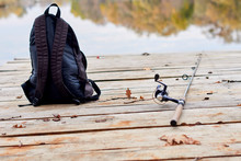 Fishing Rod, Spinning Reel On The Background Pier River Bank