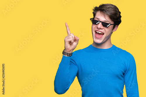 Obraz na plátně Young man wearing funny thug life glasses over isolated background pointing finger up with successful idea