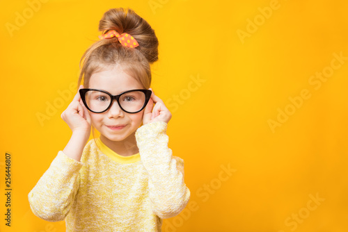 Fotomural  Cute child girl with glasses on a yellow background