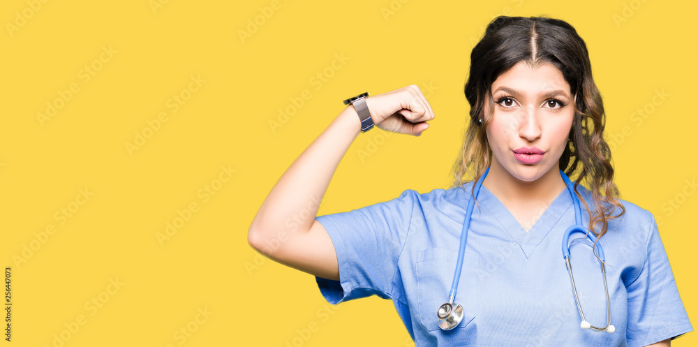 Fototapety, obrazy: Young adult doctor woman wearing medical uniform Strong person showing arm muscle, confident and proud of power