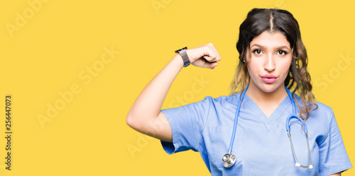 Fotografiet  Young adult doctor woman wearing medical uniform Strong person showing arm muscl