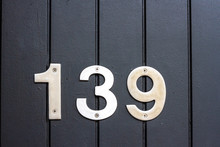 House Number 139 With The One Hundred Thirty Nine In Broad Metal Numbers Which Are Screwed To Black Wooden Boards