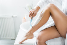 Partial View Of Young Adult Woman Shaving Leg With Razor In Bathroom